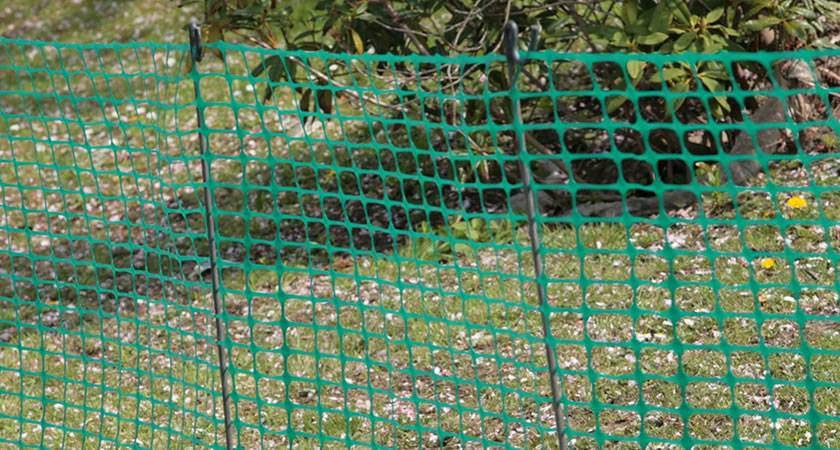 Square mesh temporary fence erected by steel pins.