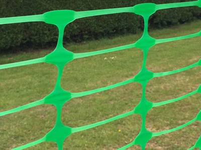 Flat oriented green barrier mesh with oval opening.
